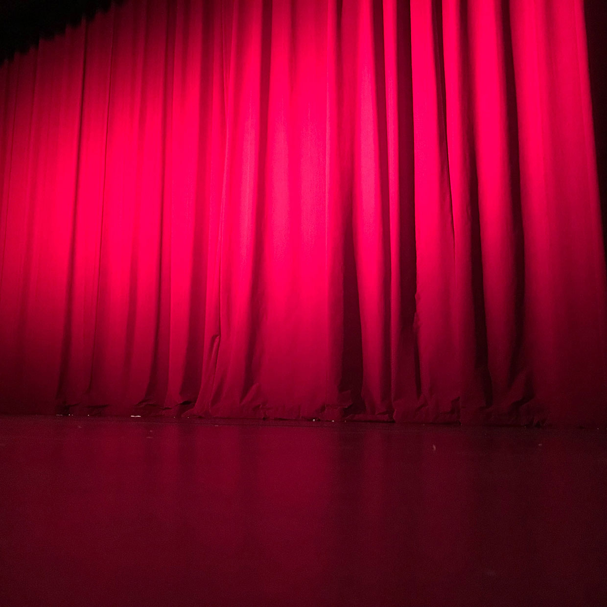 Red curtains about to open for the performance on stage