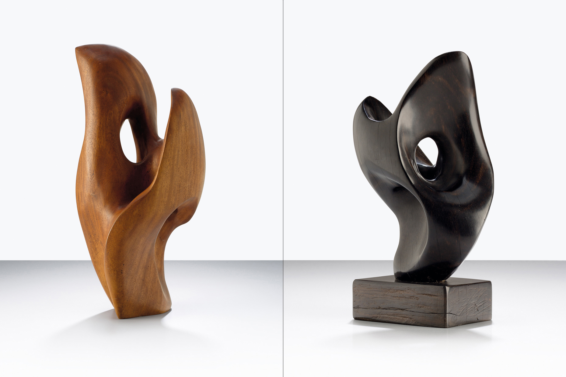 Two wooden sculptures standing on a simple tabletop. Craftsmanship beauty modern forms